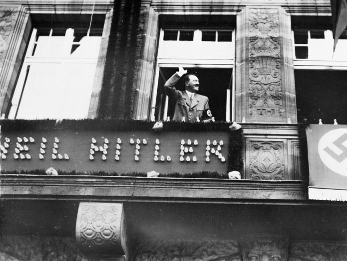 Adolf Hitler salutes the crowd from the balcony of Hotel Deutscher Hof in Nuremberg at the start of the 1934 Reichsparteitag