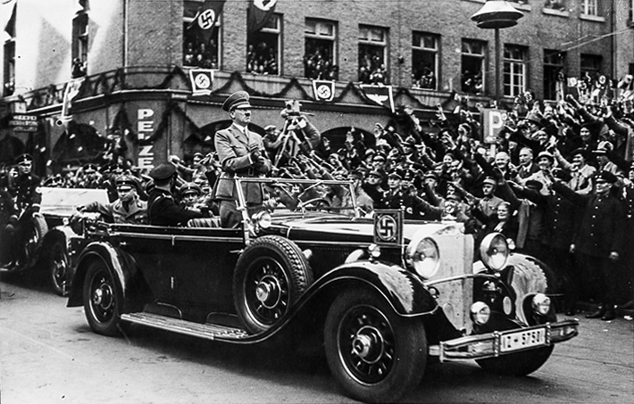 Adolf Hitler is standing in his open car while driving through Cologne