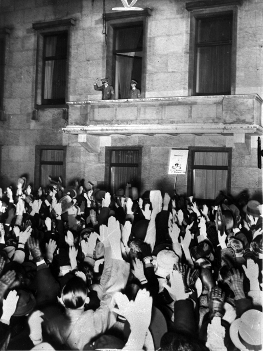Adolf Hitler and Joseph Goebbels salute the crowd from the balcony of Berlin's chancellery after the plebiscite for Austria