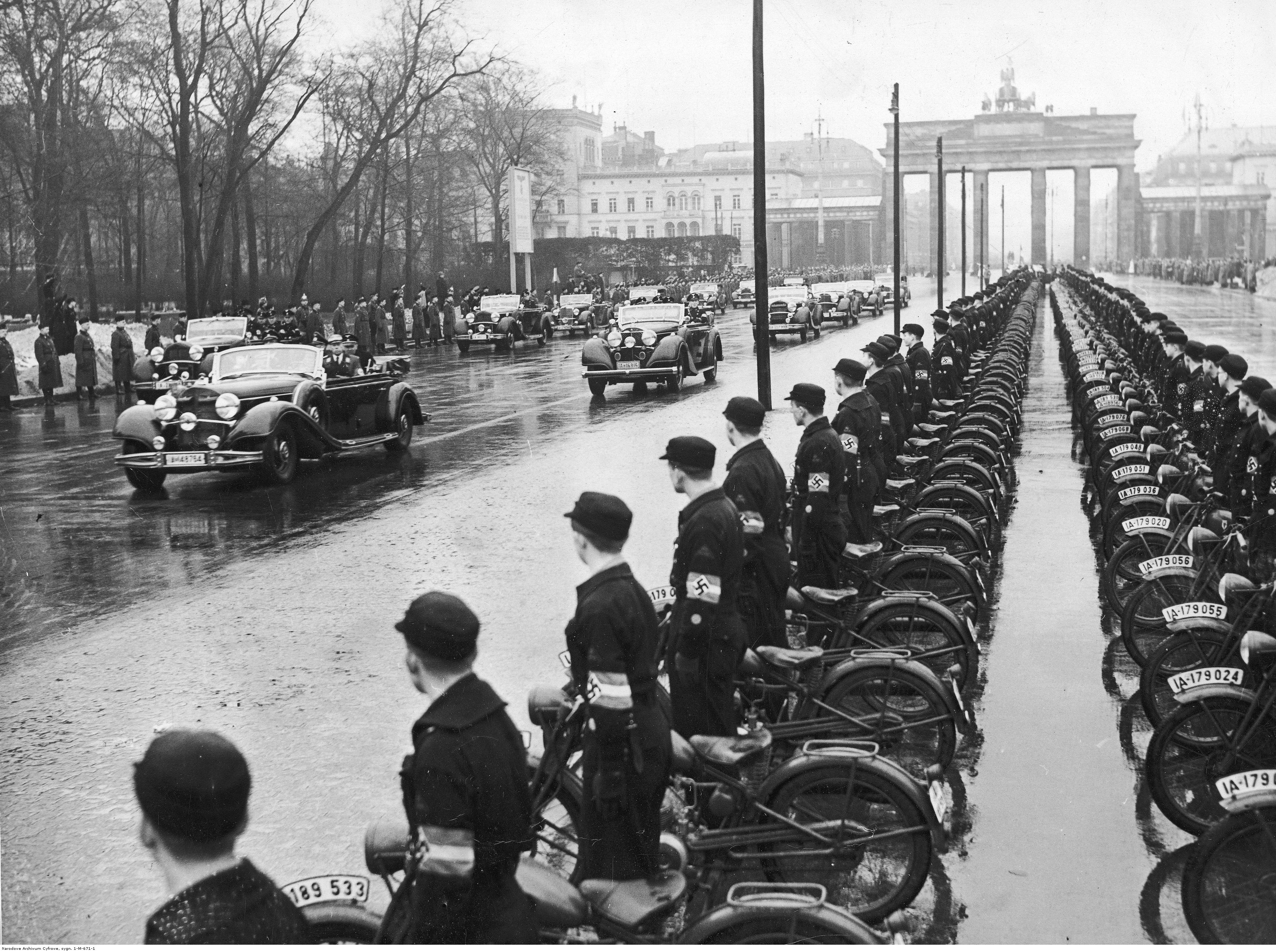 Adolf Hitler arrives at the international automobile show in front of the Brandeburg gate in Berlin, along a parade of 20000 NSKK members