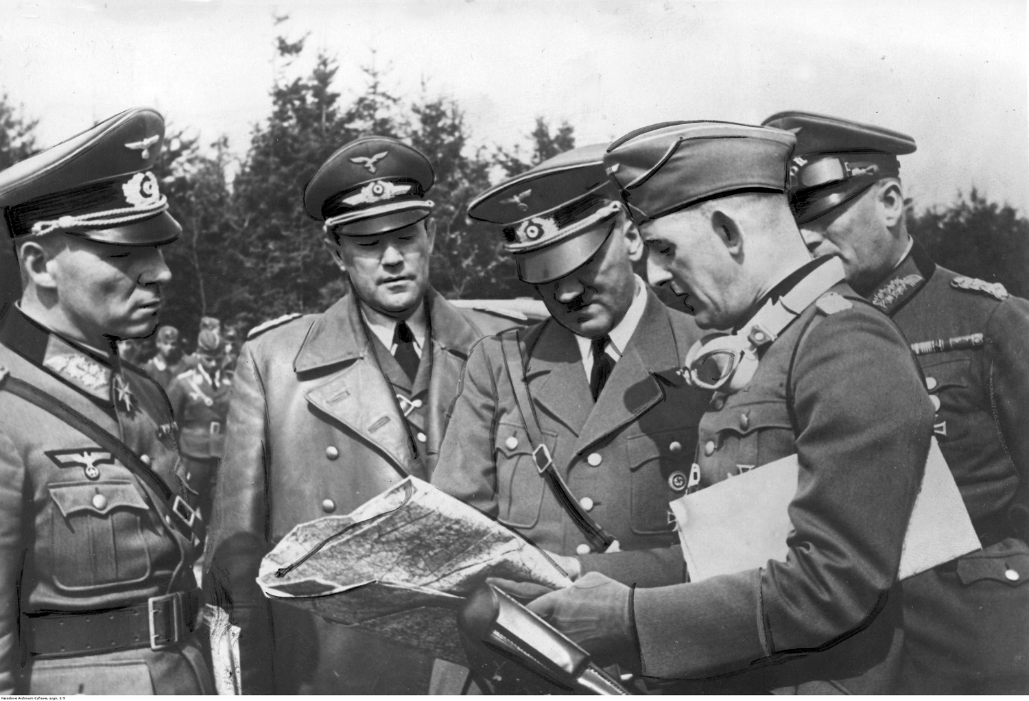 Adolf Hitler reviews strategic maps of the Poland campaign with his generals