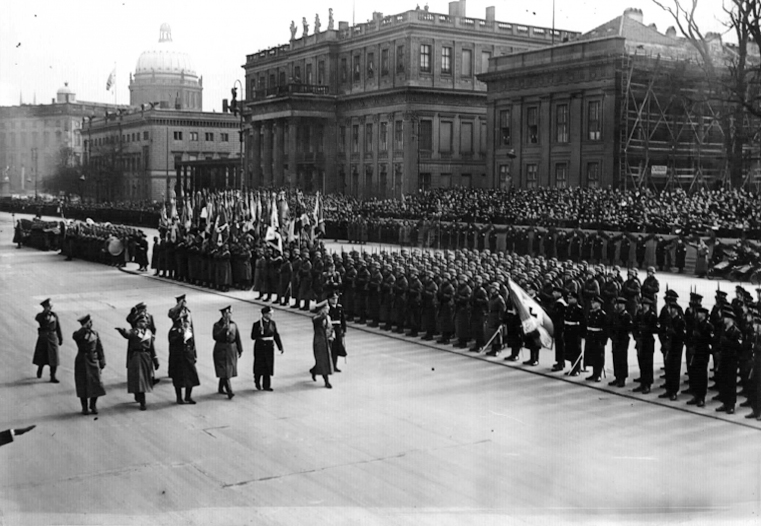 Hitler, accompanied by Grand Admiral Raeder, Generals Keitel and Milch, Reichsführer-SS Himmler, Lieutenant General Hase, General Reinhardt, and the Reichskriegsopferfuhrer Oberlindober, marches in front of the Ehrenbataillon.